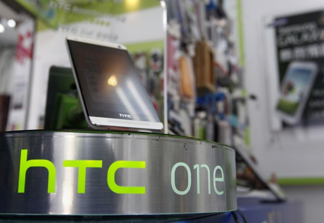 An HTC One smartphone is displayed in a mobile phone shop