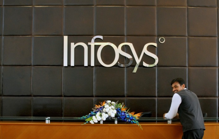 An employee of Infosys stands at the front desk of its headquarters in Bengaluru