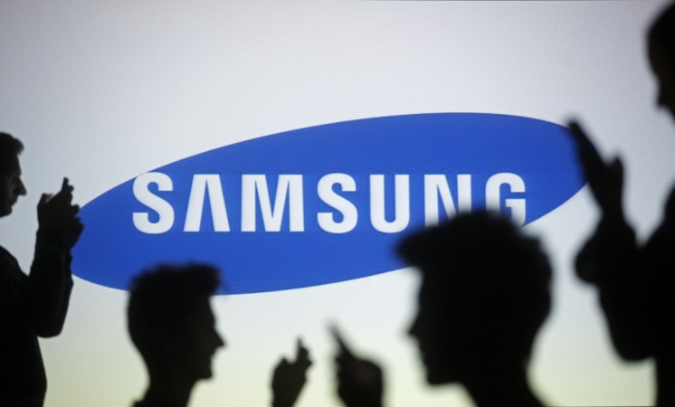 People pose with mobile devices in front of a screen projected with a Samsung logo