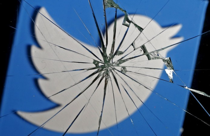 3D-printed Twitter logo is seen through broken glass