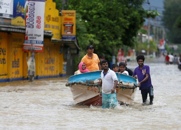 Villagers pull a boat with rescued people