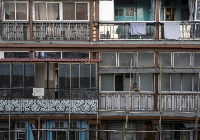 A woman looks out of a window of an apartment in south Mumbai March 15, 2015. The cost for buying a 600 square feet (55 square meters) one-bedroom apartment in this building is around 20,000 Indian rupees per square feet ($ 320) or 12,000,000 Indian rupee