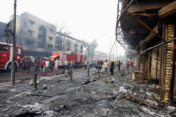 People inspect the site of a suicide car bomb in the Karrada shopping area, in Baghdad, Iraq July 3, 2016.