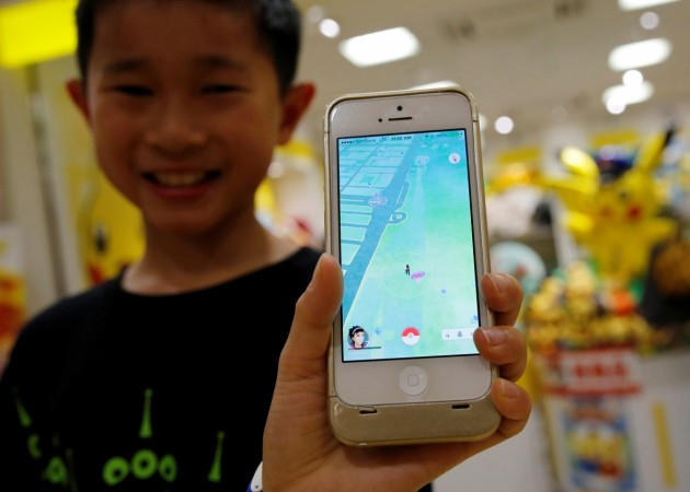 In Picture: A boy poses with a mobile phone displaying the augmented reality mobile game