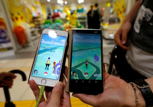 """Men pose with their mobile phone displaying the augmented reality mobile game """"Pokemon Go"""""""