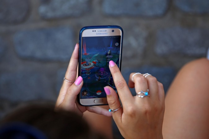 A young woman plays the augmented reality mobile game