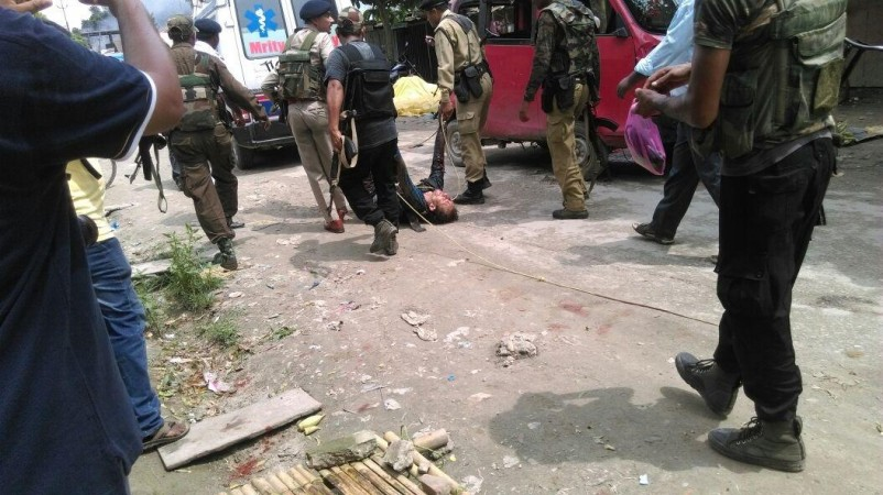 Kokrajhar: Security personnel take away body of a man killed in Kokrajhar terror attack on Aug 5, 2016. At least 12 civilians were killed on Friday when militants in military fatigues opened random fire at a busy market in Assam's Kokrajhar town. Police s