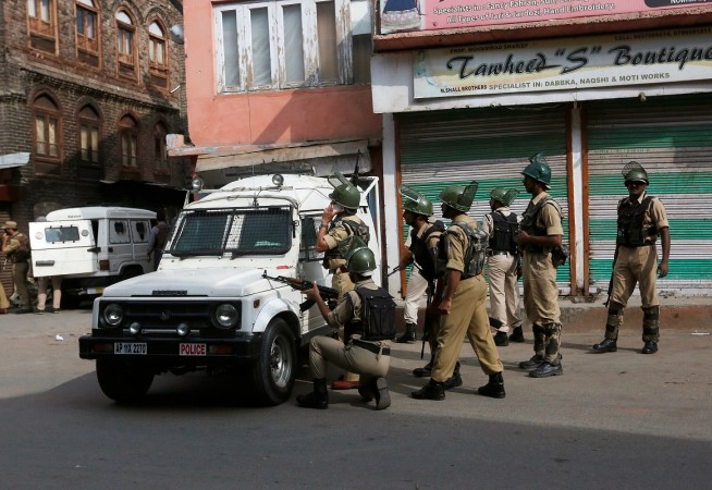 Indian policemen take position behind a jeep near the site of a gunfight between Indian Security Forces and suspected militants in Srinagar, August 15, 2016.