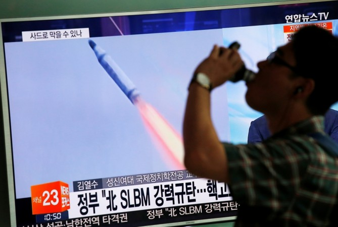 A passenger walks past a TV screen broadcasting a news report on North Korea's submarine-launched ballistic missile fired from North Korea's east coast port of Sinpo, at a railway station in Seoul, South Korea, Aug. 24, 2016.