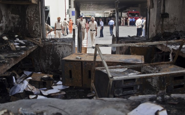Maruti Suzuki vendor India-Japan Lighting plant gutted in fire. Pictured: Police and private security guards walk past a damaged reception block of Maruti Suzuki's plant in Manesar, located in the northern Indian state of Haryana (File photo)