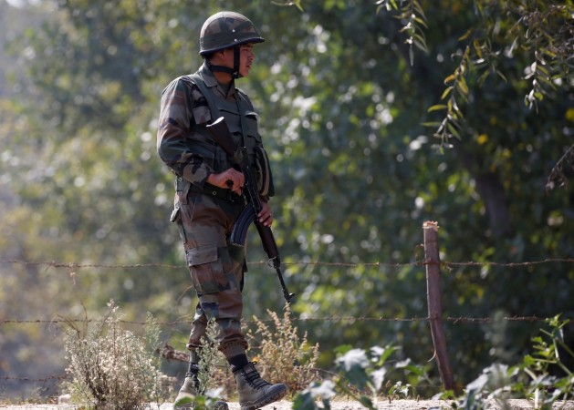 An Indian army soldier patrols along a highway on the outskirts of Srinagar