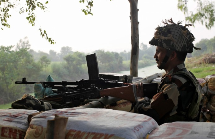 An Indian army soldier keeps guard from a bunker near the border with Pakistan in Abdullian