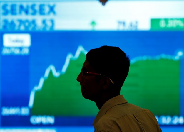 A man looks at a screen displaying news of markets update inside the Bombay Stock Exchange building in Mumbai