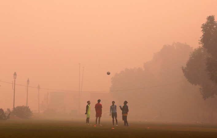 Boys play football in a public park on a smoggy morning in New Delhi