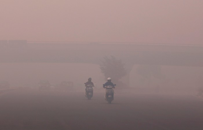 Commuters make their way amidst the heavy smog in New Delhi