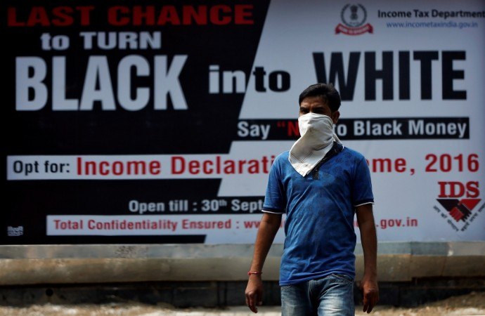 A man walks past an income tax billboard in New Delhi. Reuters file