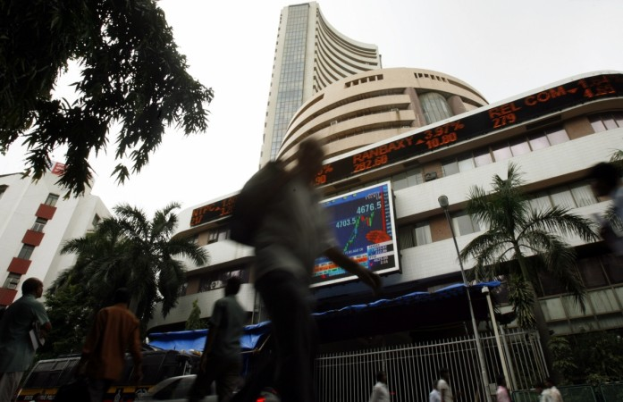 People walk pass the Bombay Stock Exchange building displaying India's benchmark share index on its facade