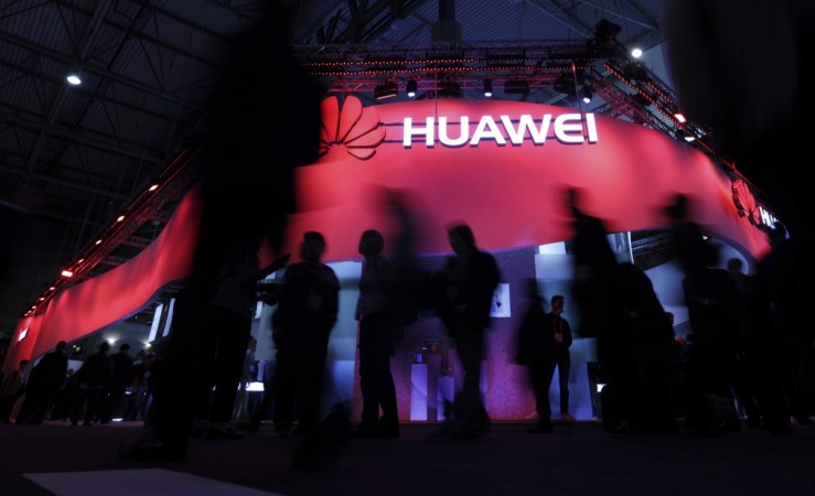 Visitors walk past Huawei's booth during Mobile World Congress in Barcelona Spain