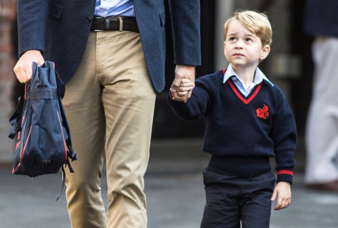 Prince George holds his father Britain's Prince William's hand as he arrives on his first day of school at Thomas's school in Battersea London