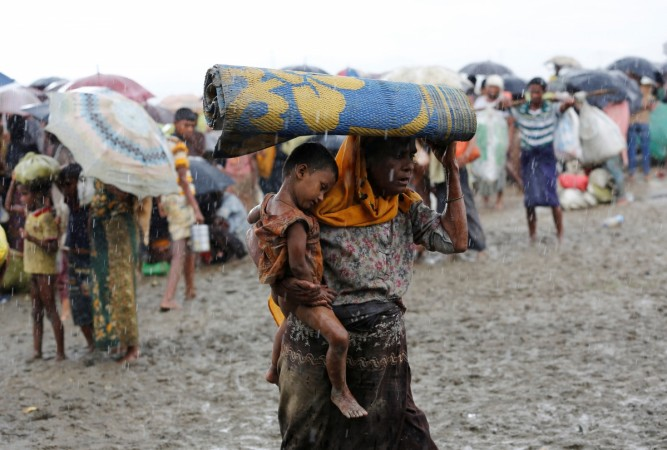 Rohingya refugees walk in the rain as they are held by the Border Guard Bangladesh after illegally crossing the border in Teknaf Bangladesh