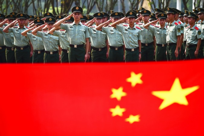 Retiring paramilitary policemen take their oaths in front of a Chinese national flag