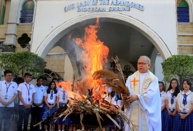Fr. Jerry Habunal, a Catholic priest, leads the burning dried palm leaves as they burn to be used for Ash Wednesday rites