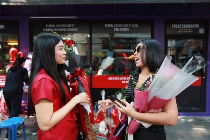 Women chat as they hold flowers during a Valentine's Day celebration in front of a gift shop in Bangkok, Thailand