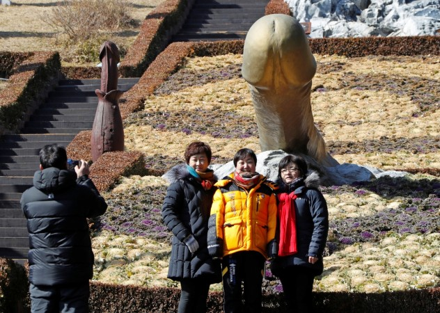 Tourists pose near a statue in South Korea's Haeshindang Park, also know as