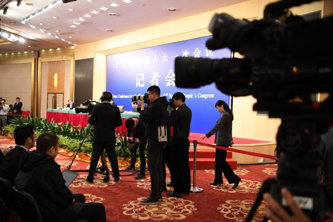 Photographers take pictures during a press conference
