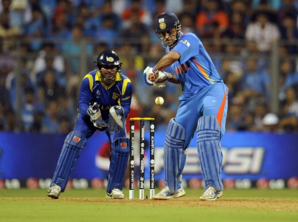 India's captain Mahendra Singh Dhoni plays a shot as Sri Lanka's captain and wicketkeeper Kumar Sangakkara (L) looks on during their ICC Cricket World Cup final match in Mumbai April 2, 2011.