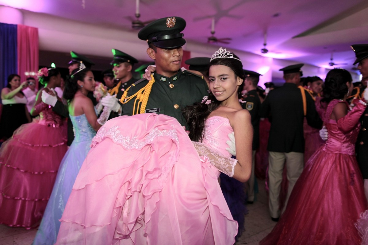 A cancer patient dances with a cadet from Nicaragua's Military Academy during her Quinceanera