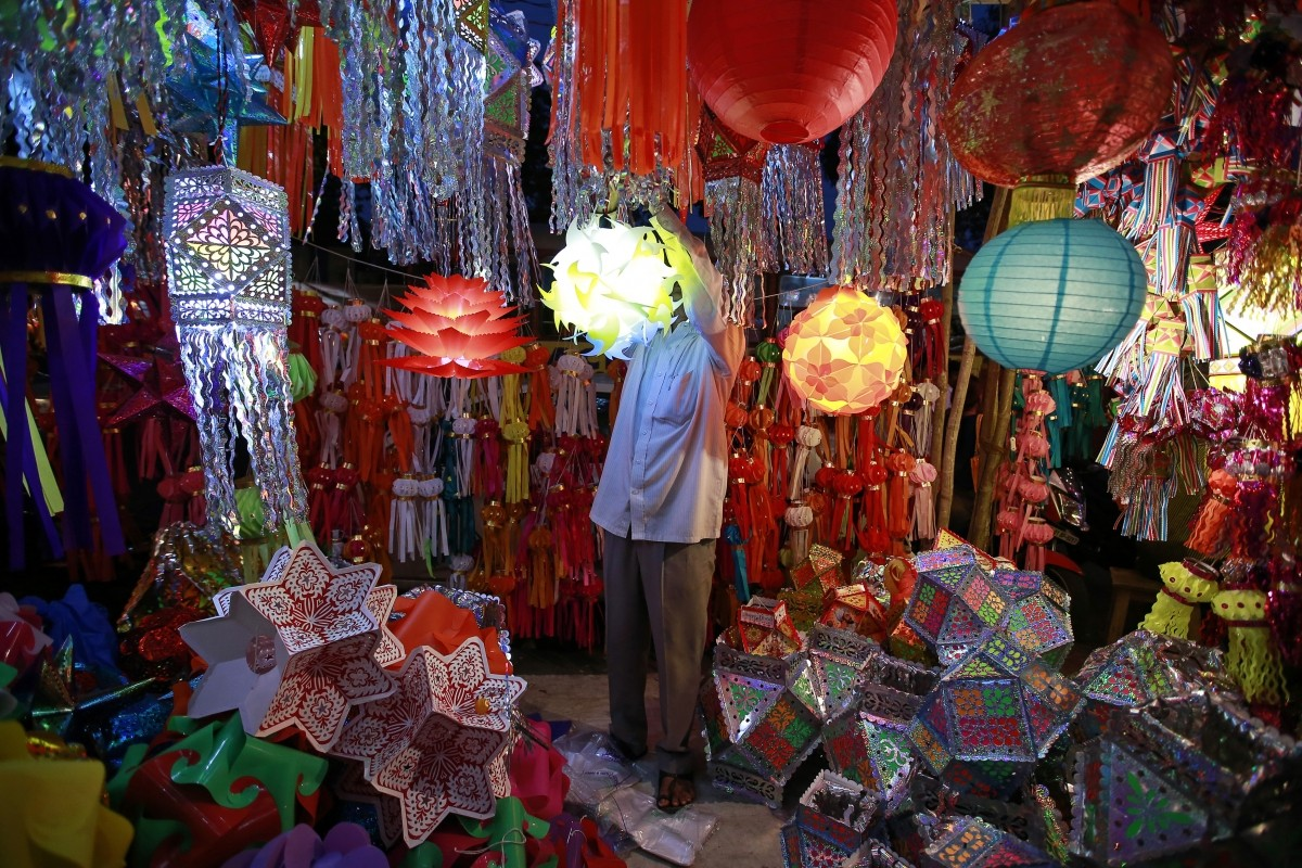 A vendor hangs a lantern for sale at a Diwali market in Mumbai October 20, 2014.