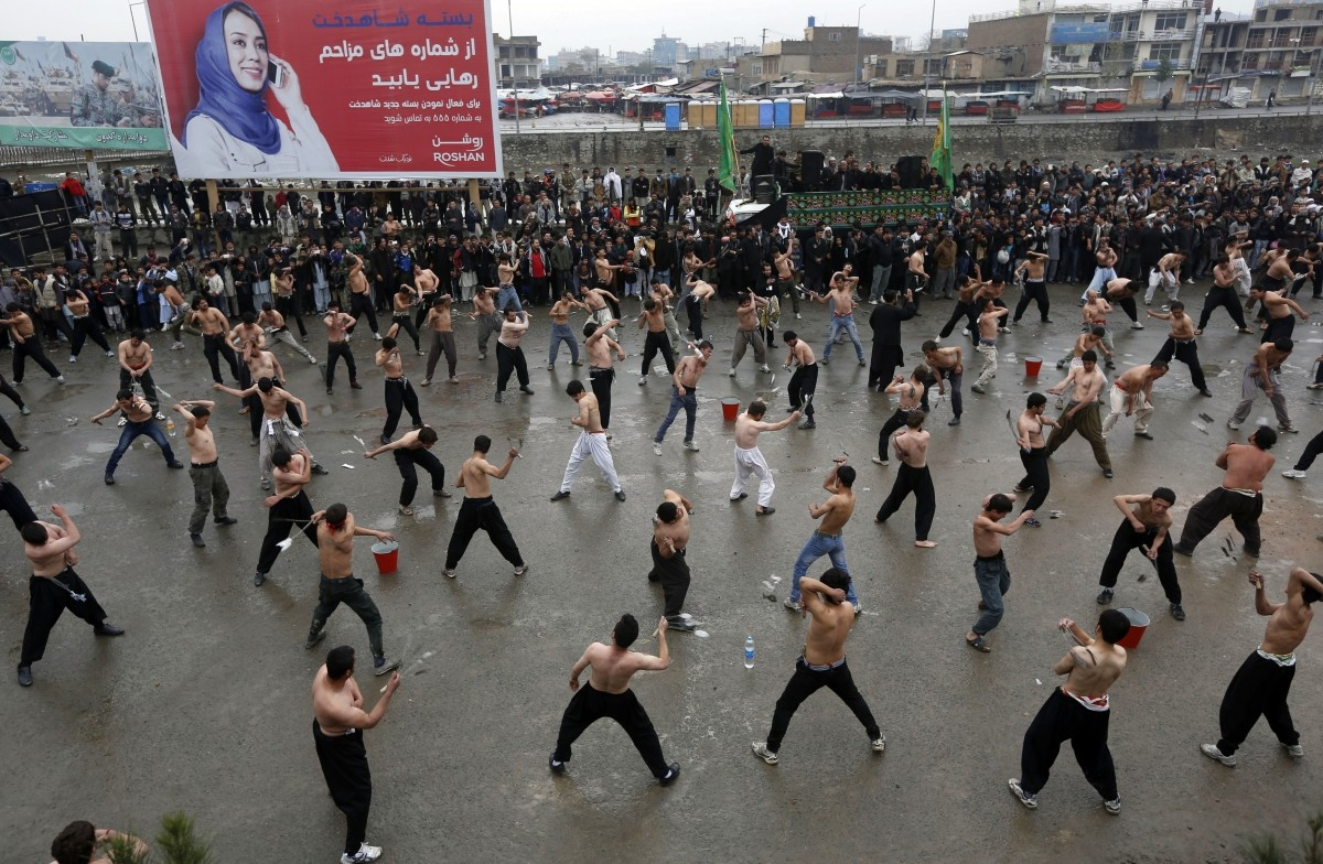 Afghan Shi'ite Muslim men flagellate themselves during an Ashura procession in Kabul