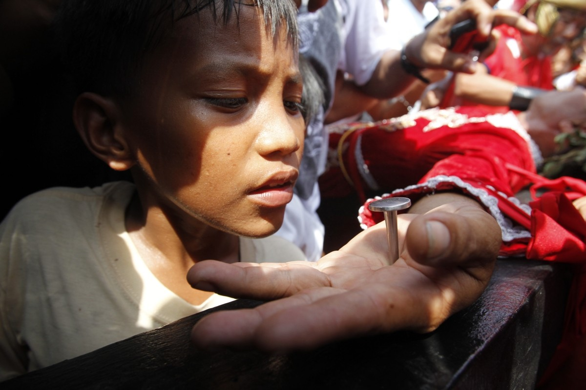 A boy looks at the palm of a penitent nailed on a wooden cross during a reenactment of Jesus Christ's crucifixion on Good Friday in Barangay Cutud, San Fernando, Pampanga in northern Philippines April 6, 2012