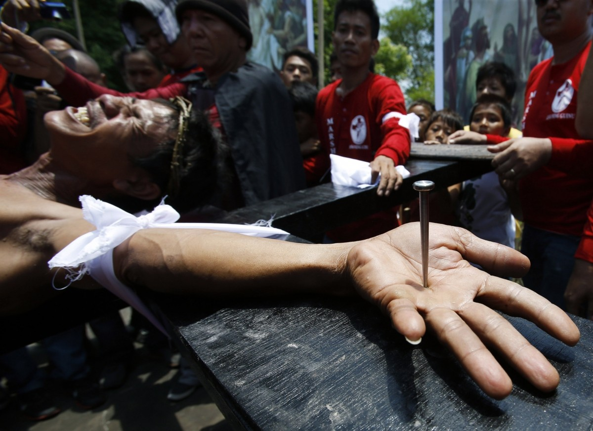 Penitent Danilo Ramos grimaces in pain as he is nailed to a wooden cross during the reenactment of the death of Jesus Christ on Good Friday in San Fernando, Pampanga in northern Philippines April 18, 2014. Penitents are nailed to wooden crosses on Good Fr
