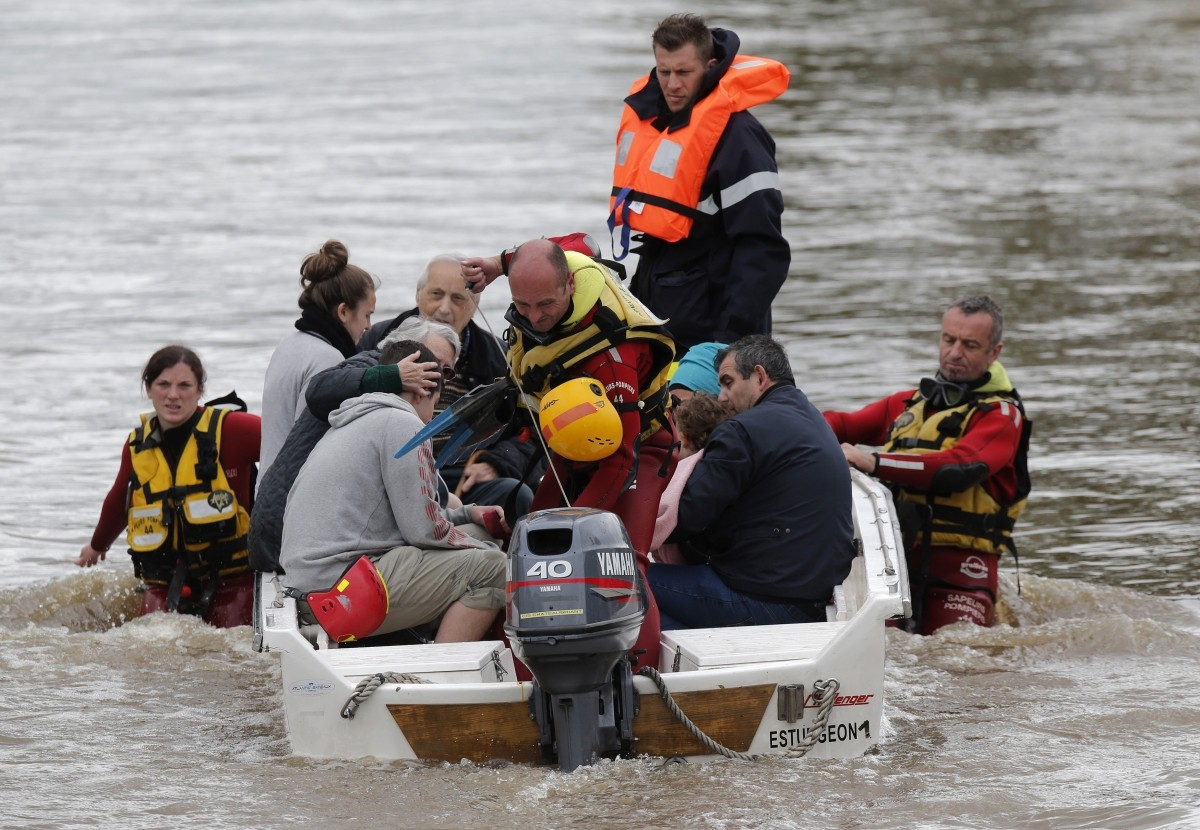 French firefighters on a small boat evacuate residents in Montargis, near Orleans.