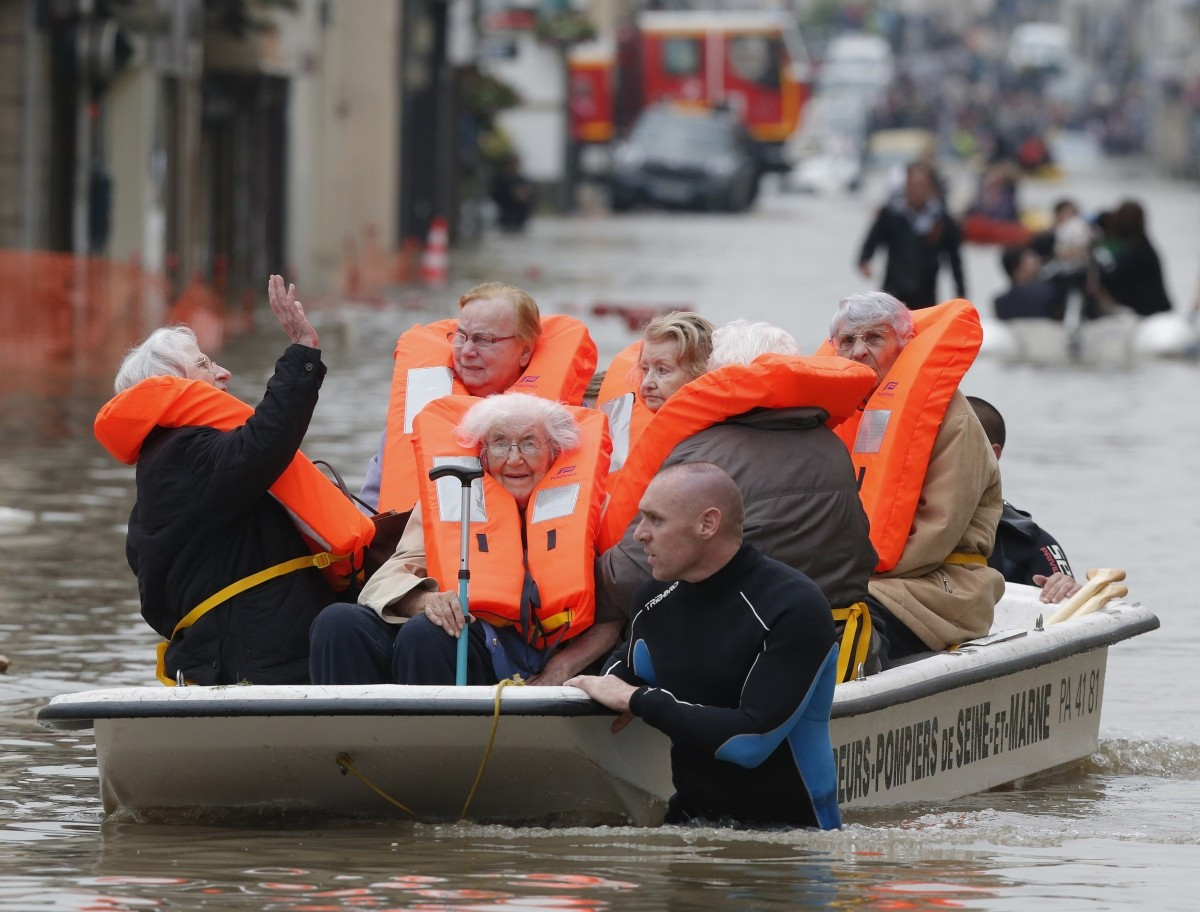 French firefighters on small boats evacuate residents from a flooded area after heavy rainfall in Nemours, France, June 1, 2016.