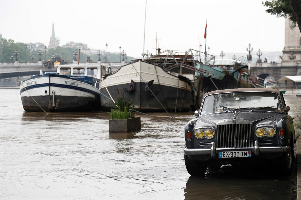 A Rolls-Royce is parked along the Seine River in Paris.