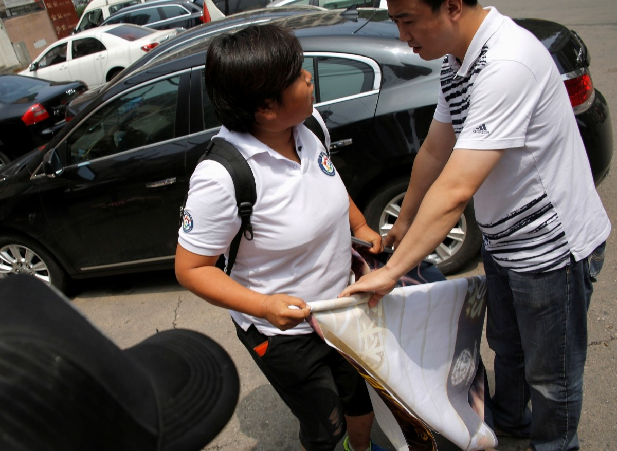 A plain clothes policeman (R) stops an animal activist unfolding a banner against Yulin Dog Meat Festival in front of Yulin City Representative office in Beijing, China, June 10, 2016.