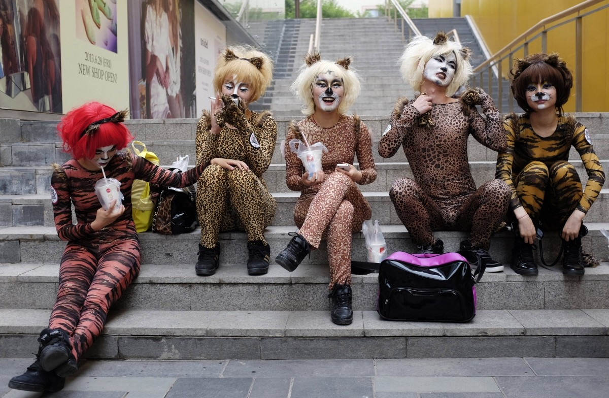 Volunteers in animal costumes wait to perform in an event to promote a love for dogs, in Beijing's Sanlitun area, June 20, 2013. Dog lovers and animal rights activists have called for the cancellation of an annual dog meat festival scheduled to take place on Friday in Yulin, Guangxi Zhuang autonomous region, voicing concerns over animal cruelty and food safety, according to China Daily.