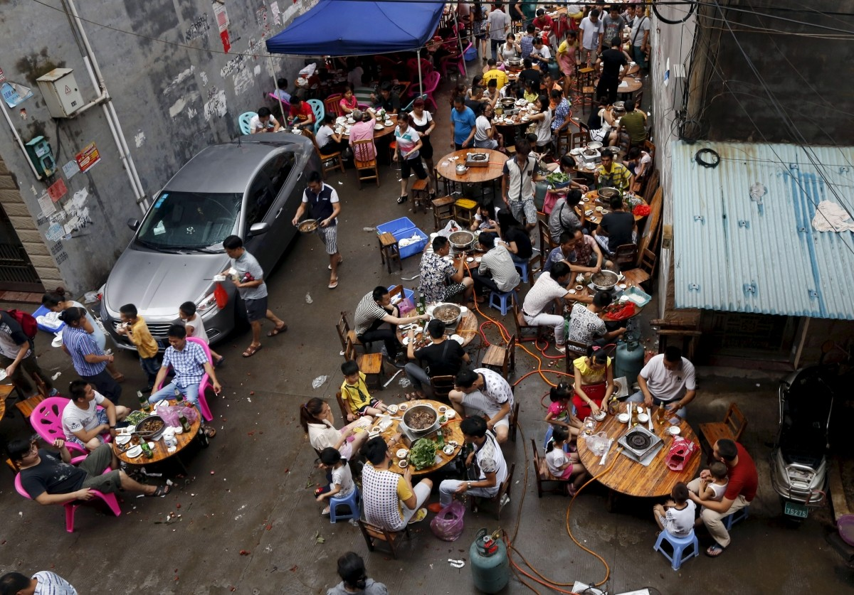 People eat dog meat at a dog meat restaurant district on the day of local dog meat festival in Yulin, Guangxi Autonomous Region, June 22, 2015. For many residents of China's southern town of Yulin, the peak of summer is the perfect time to get together with family and friends - and consume copious amounts of dog meat. Thousands of dogs are expected to end up on the chopping block during the city's annual dog meat festival, which has become increasingly controversial in China.