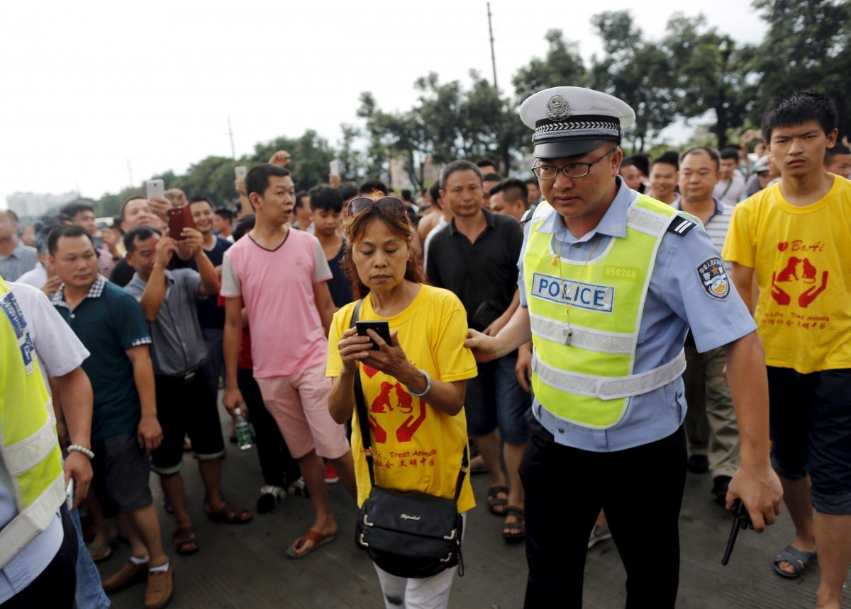 Animal right activist Du Yufeng is asked to leave by a policeman after her attempt to hold a protest against dog meat eating as local residents follow her at a dog meat restaurant district on the day of local dog meat festival in Yulin, Guangxi Autonomous Region, June 22, 2015. For many residents of China's southern town of Yulin, the peak of summer is the perfect time to get together with family and friends - and consume copious amounts of dog meat. Thousands of dogs are expected to end up on the chopping block during the city's annual dog meat festival, which has become increasingly controversial in China.