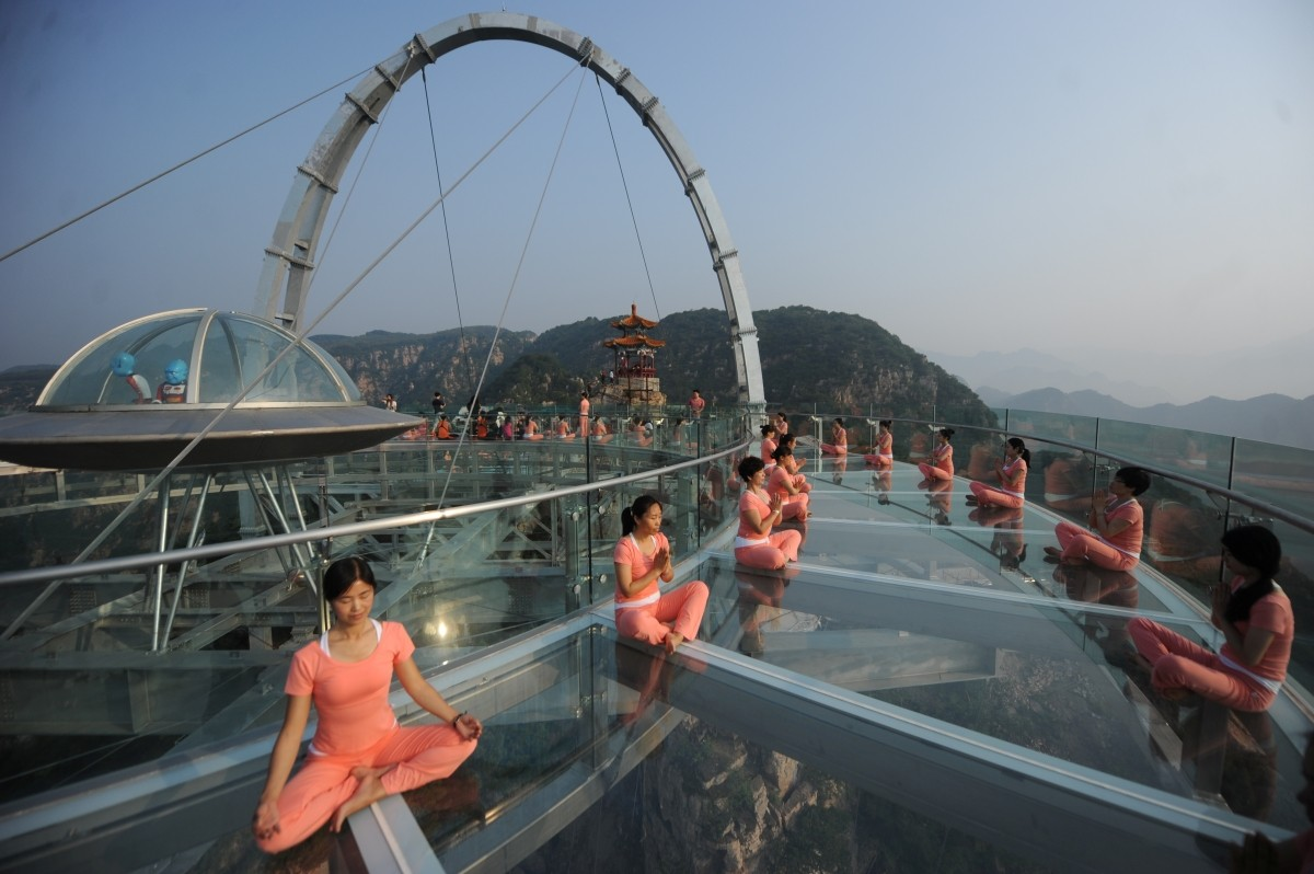 People practise yoga at a glass sightseeing platform ahead of the International Day of Yoga, on the outskirts of Beijing, China, June 20, 2016.