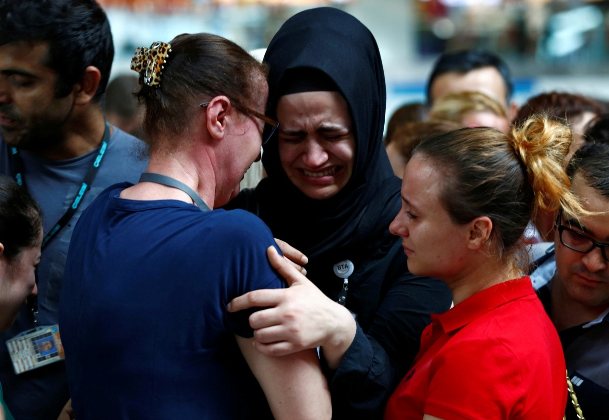 Airport employees mourn for their friends, who were killed in Tuesday's attack at the airport, during a ceremony at the international departure terminal of Ataturk airport in Istanbul, Turkey, June 30, 2016.