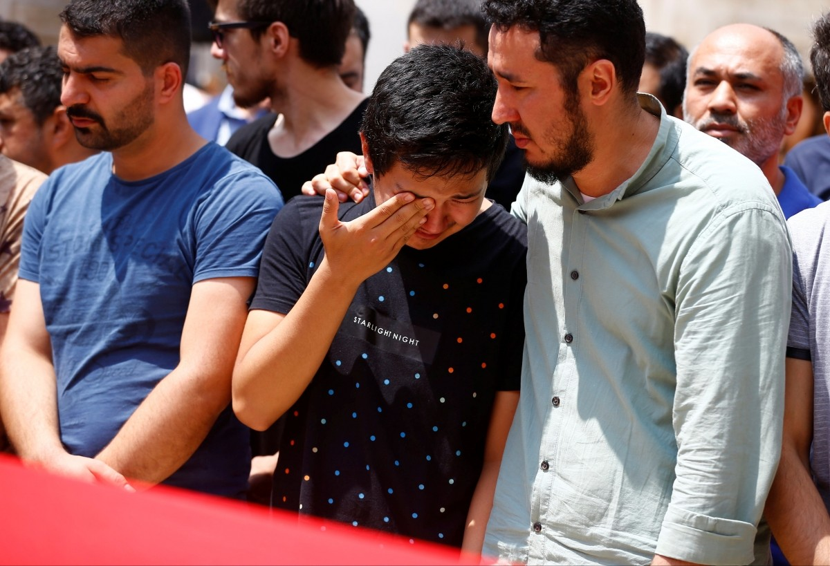 Friends and relatives of Habibullah Sefer, who was killed in Tuesday's attack at Istanbul airport, stand next to his flag-draped coffin during his funeral ceremony in Istanbul, Turkey, June 30, 2016.
