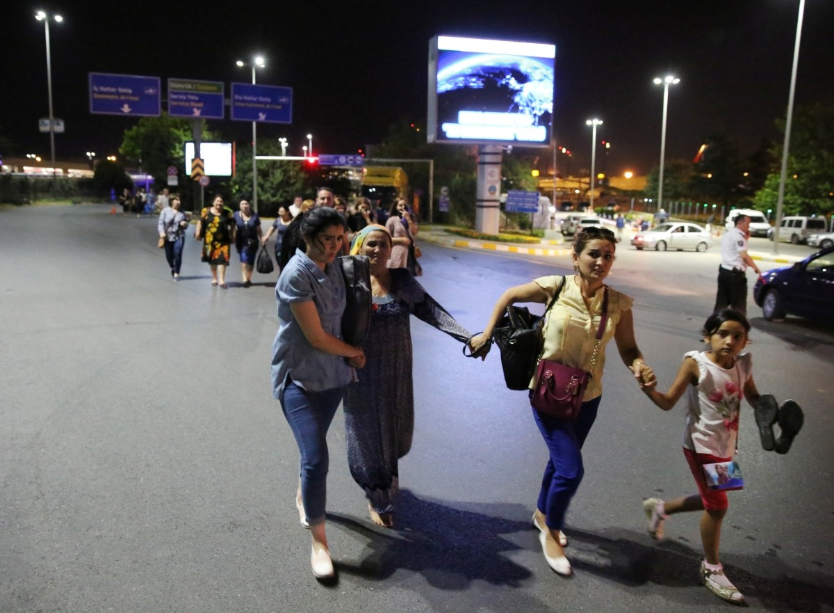 People walk away from Istanbul Ataturk airport, Turkey, following a blast June 28, 2016.