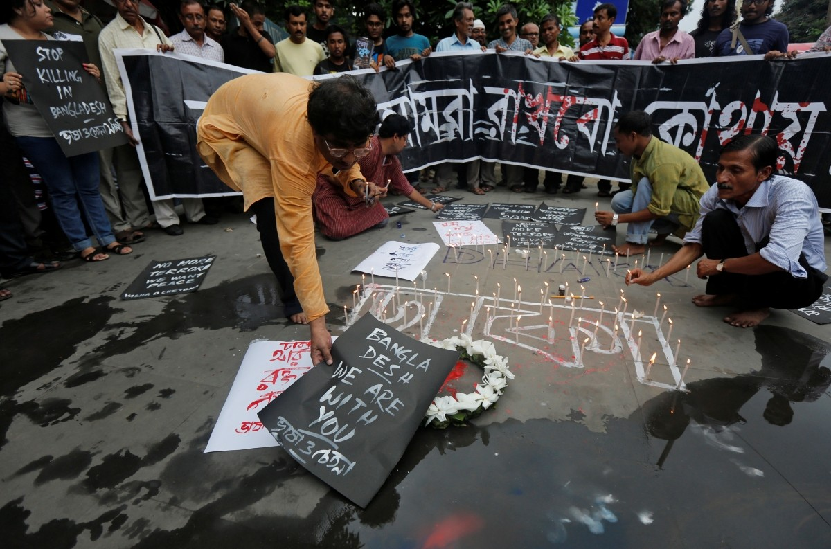 A man places a sign as others light candles during a vigil in Kolkata, India, to show solidarity with the victims of the attack at Holey Artisan restaurant after Islamist militants attacked the upscale cafe in Dhaka, Bangladesh, July 2, 2016.