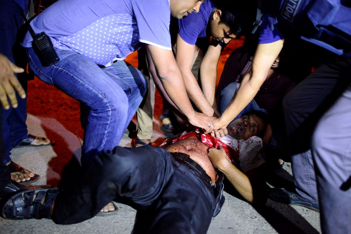 People try to help an injured person, after gunmen stormed the Holey Artisan restaurant and took hostages, in the Gulshan area of Dhaka, Bangladesh July 1, 2016.