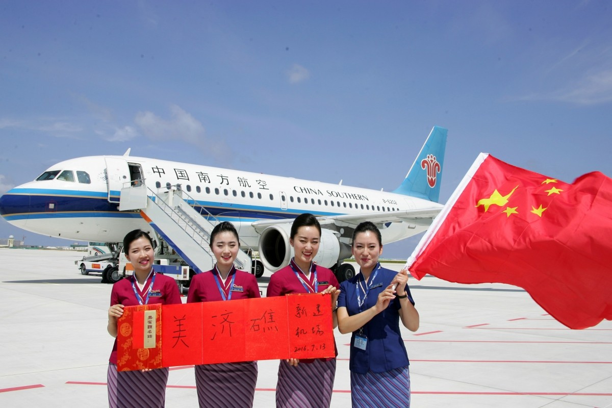 China on Wednesday flew two civilian aircraft to assert its claims to the artificial islands built in the disputed area. It successfully tested two new airfields on the disputed islands with civil flights a day after an international tribunal struck down Beijing's claims over the region.In Picture:Crew members holding a Chinese national flag pose for pictures in front of a plane of the China Southern Airlines as the plane landed at a new airport China built on Mischief Reef of the Spratlys, South China Sea, July 13, 2016.