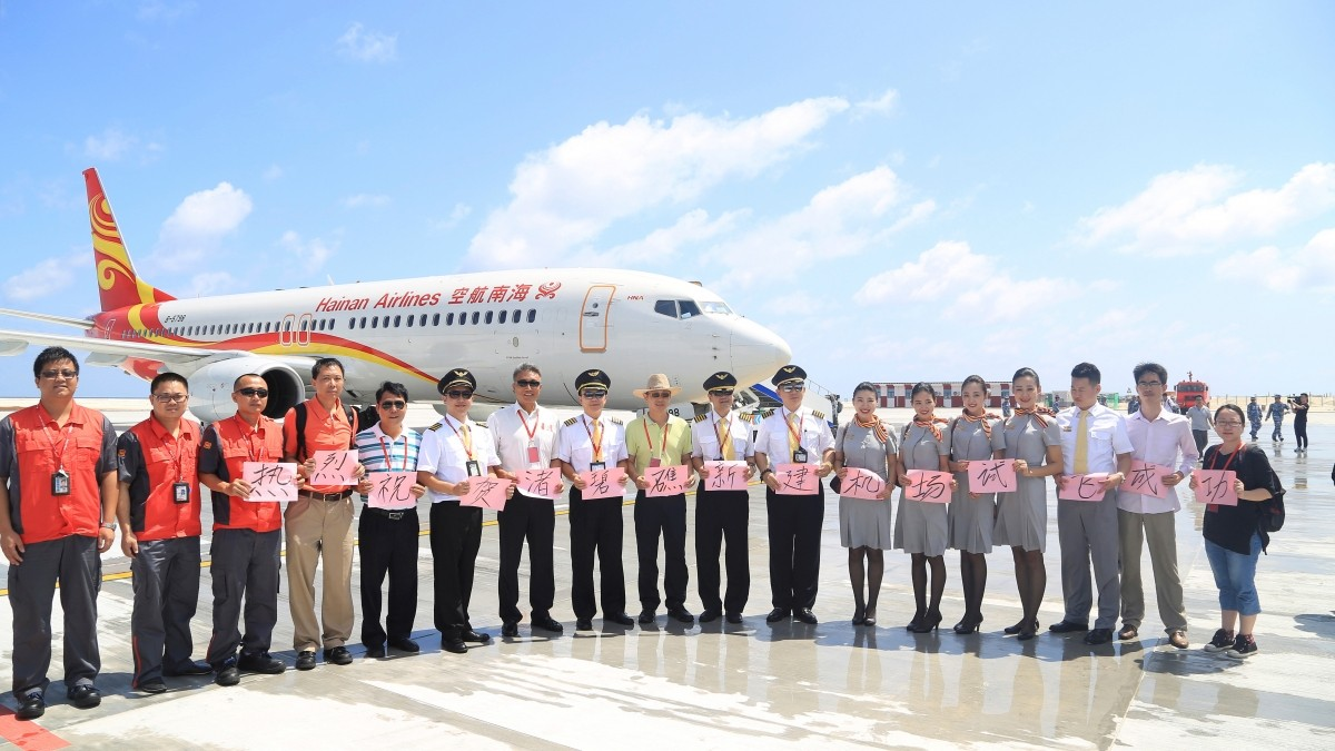Talking about the disputed zone state-run Xinhua news agency said that the number of airfields open to civil aircraft has gone up to three. In picture:Crew members pose for pictures in front of a plane of Hainan Airlines as the plane landed at a new airport China built on Subi Reef of the Spratlys, South China Sea, July 13, 2016. The Chinese characters on the placards read